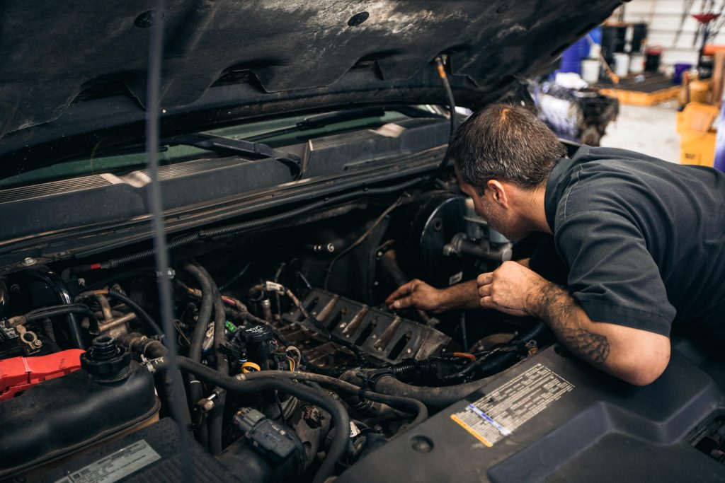 Open hood with a Mechanic checking the Engine in the service department